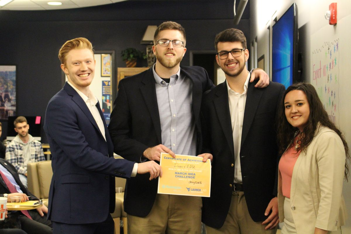 Three male students and one female stand together with a winner's certificate